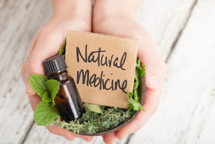 home remedies Bowl of herbs and essential oil and card saying Natural Medicine on light floor boards