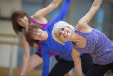 A multi-ethnic group of senior adult women are taking a yoga class together at the gym. Fit for life.