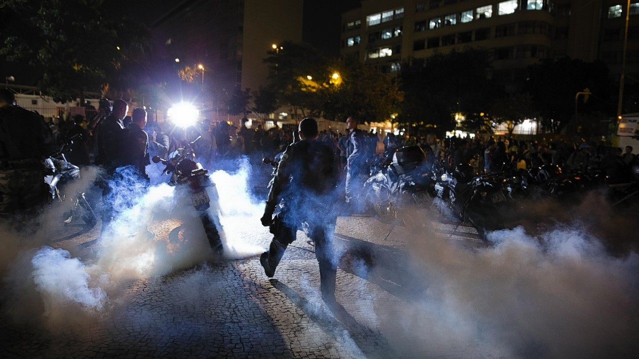 Police officers walk through a cloud of tear gas during a protest against the money spent on the World Cup preparations, in Rio de Janeiro, Brazil,