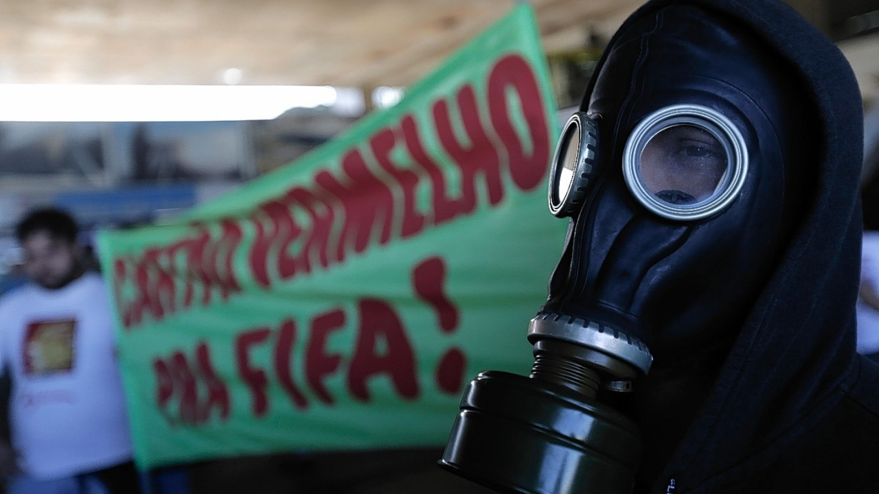 "A man with a gas mask stands next to a banner that reads in Portuguese, ""Red Card for FIFA"",  during a protest against the money spent on the World Cup, in Brasilia, Brazil,"