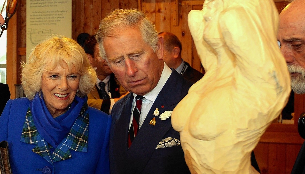The Prince of Wales and the Duchess of Cornwall study a wood carving of a ship's figure head, during a visit to the Hector Quay Museum in Pictou county, Nova Scotia, at the start of their Royal trip to Canada