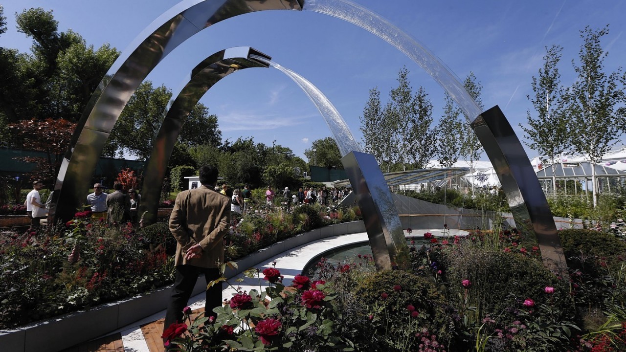 A visitor takes a photograph of flowers at the Chelsea Flower Show