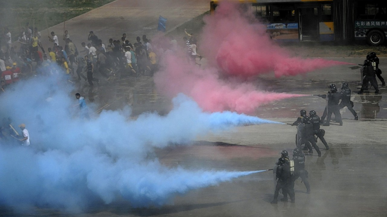 Chinese policemen spray colored gas at a group of people acting out the role of rioters during an anti-terrorism exercise held in Beijing, China
