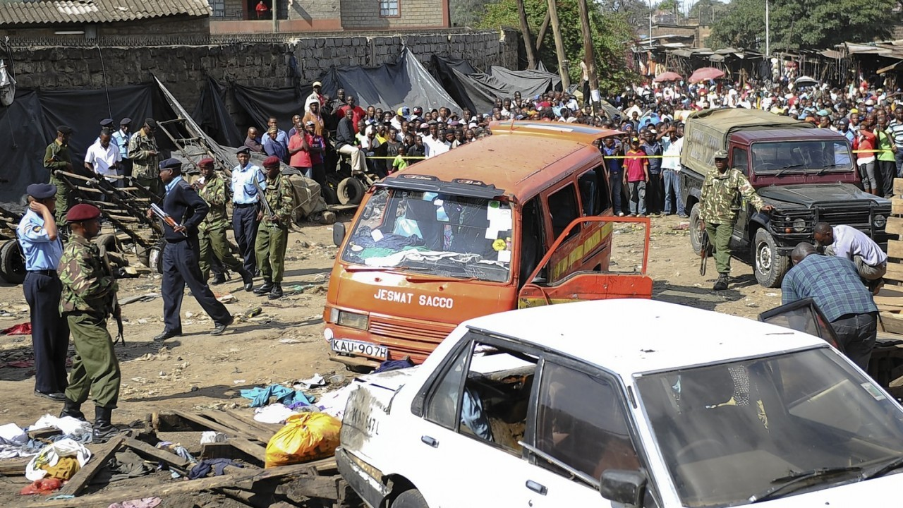 Security forces secure the scene at the site where two blasts detonated, one in a mini-van used for public transportation, in a market area of Nairobi, Kenya