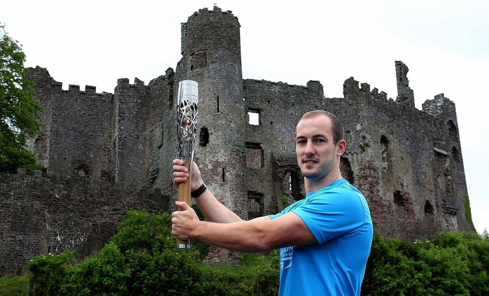 Queen's Baton relay of Baton Bearer Lee Williams holding the Queen's Baton Laugharne Castle in Wales. Wales is nation 68 of 70 nations and territories the Queen's Baton will visit
