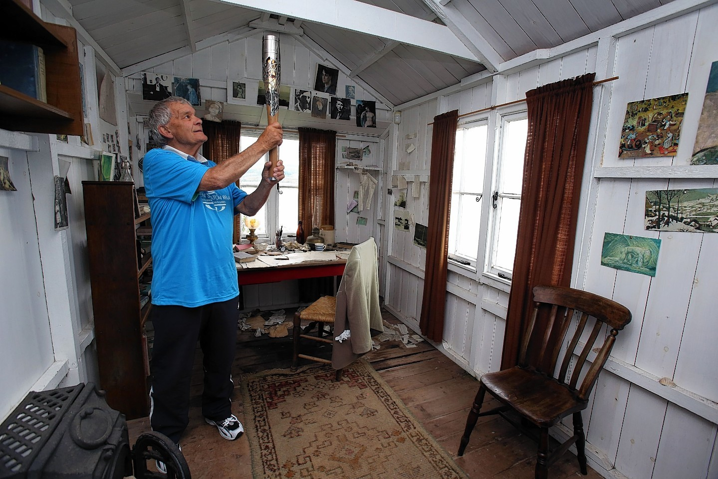 Baton Bearer John Phillips holding the Queen's Baton inside the Dylan Thomas writing shed at Laugharne in Wales. Wales is nation 68 of 70 nations and territories the Queen's Baton will visit