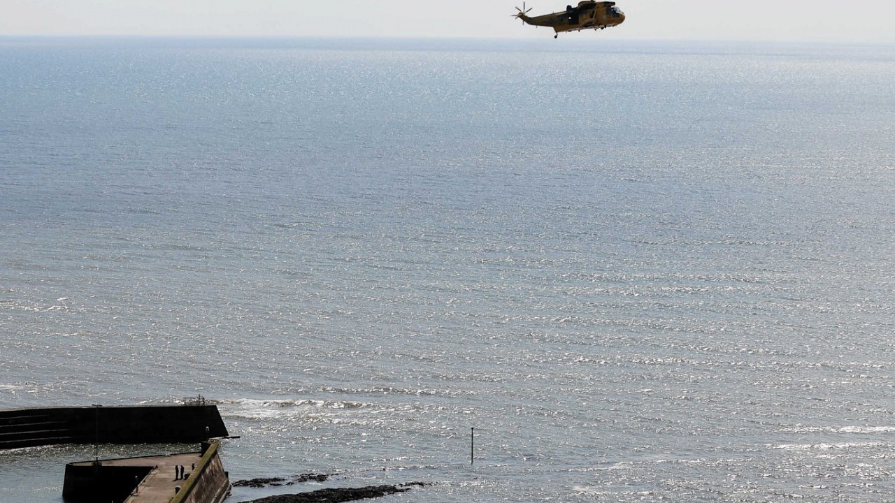 A search and rescue helicopter heads out to sea in search of the missing fishermen