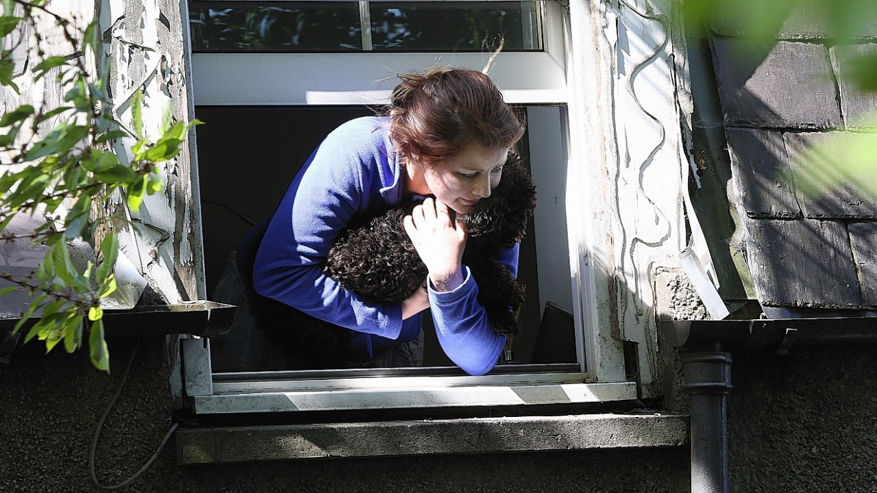 Rachel holds her dog Minnie as she leans out the window looking for people to help her escape the fire