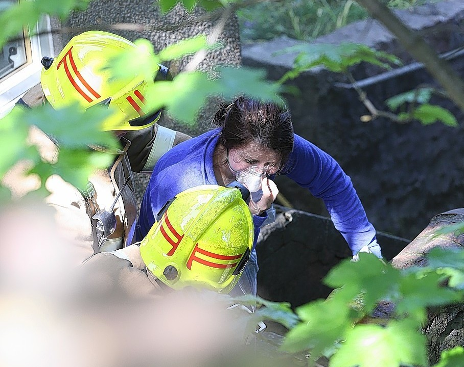 Fire fighters try to comfort Rachel as she inhales oxygen following her ordeal