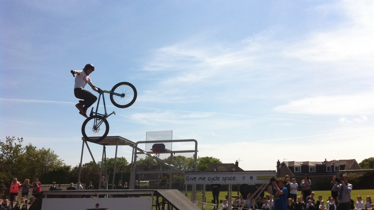 A stunt biker goes no handed over a jump at Fernielea Primary School this afternoon.