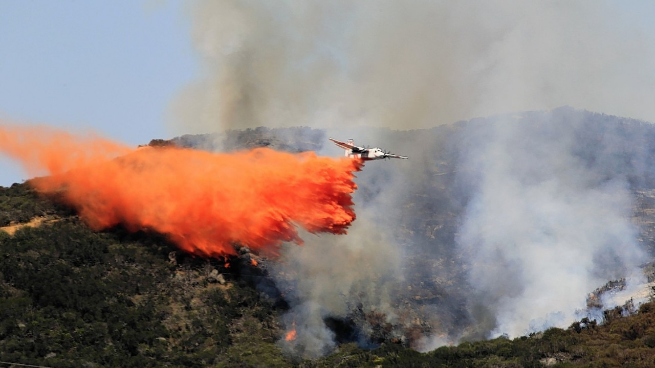 A plane drops fire retardant in the area of Harmony Grove in Escondido, Calif