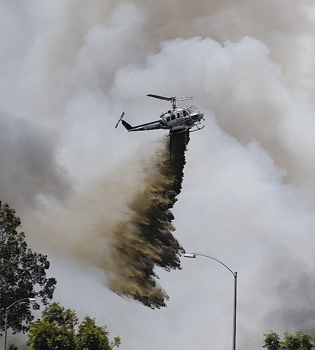 Flames engulfed suburban homes and shot up along canyon ridges in one of the worst of several blazes that broke out Wednesday in Southern California during a second day of a sweltering heat wave