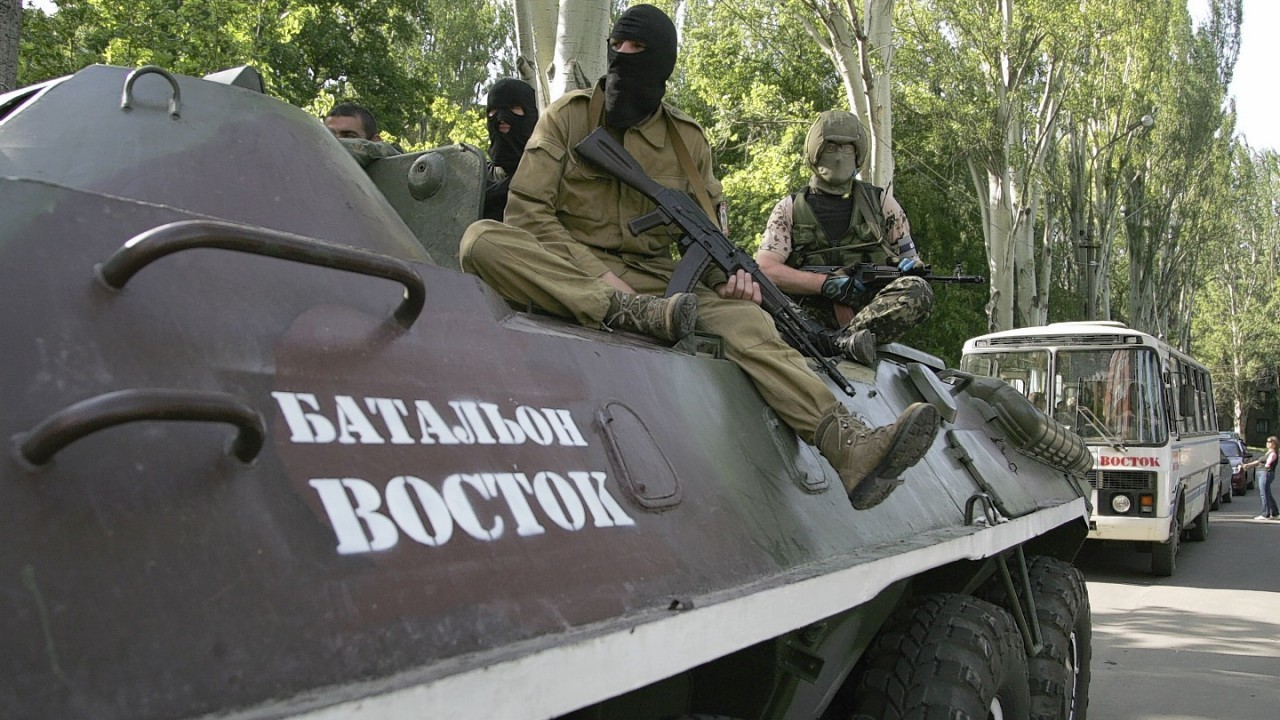 """Pro-Russian gunmen atop of an armored personnel carrier with the words read """"Battalion Vostok (East) """" patrol a street in Donetsk, Ukraine"""