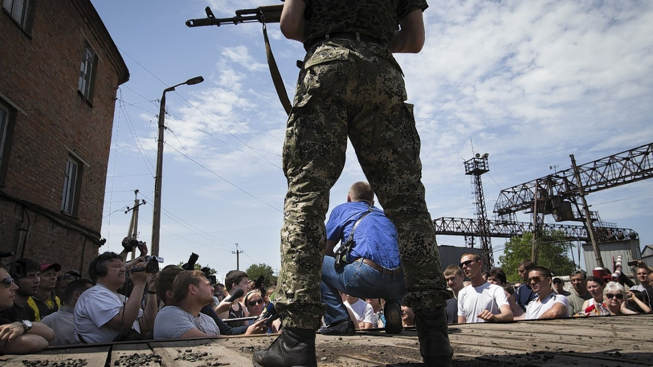 Vyacheslav Ponomarev, center in blue, the self-proclaimed mayor of Slovyansk speaks to local citizens whose homes were ruined in a shelling as his armed bodyguard stands behind his back in Slovyansk, eastern Ukraine