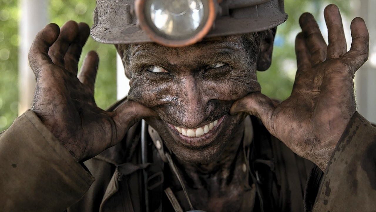 A Ukrainian miner forces a smile after working in Eastern Ukraine