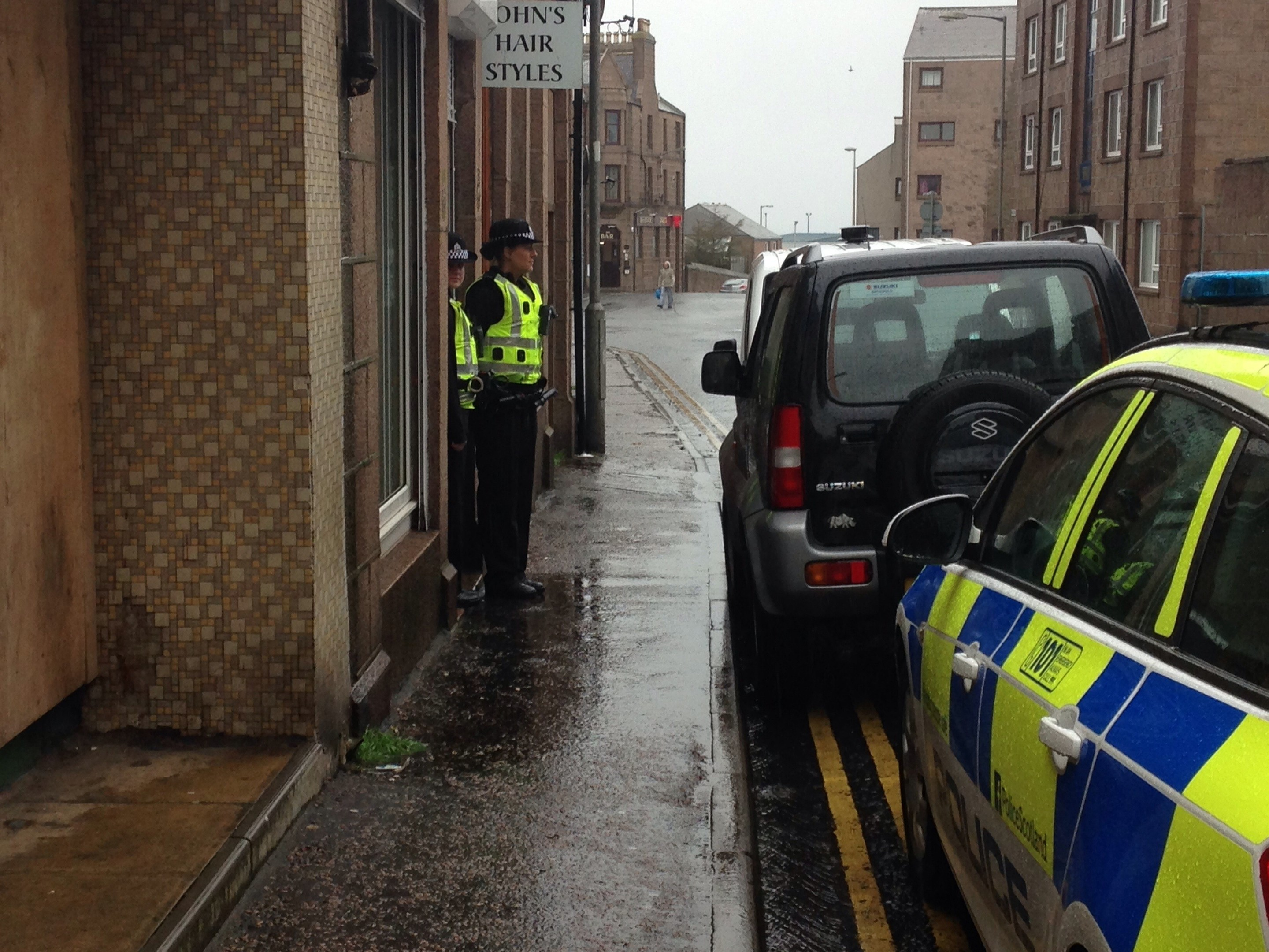 Police guard the entrance to the raided shop in Peterhead