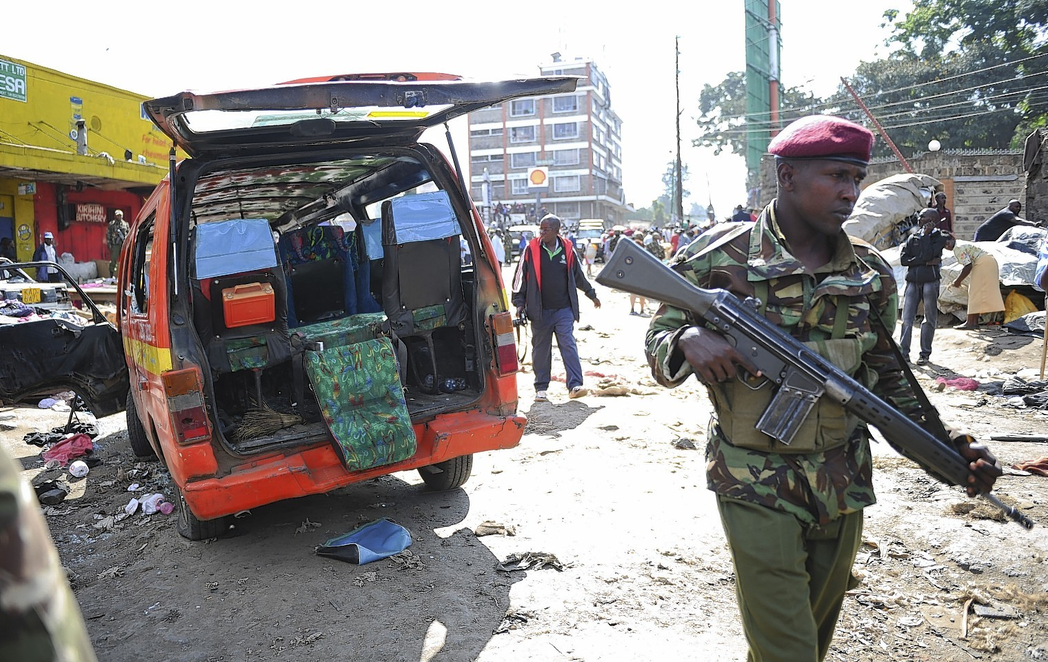 A member of the security forces patrols at the site where two blasts detonated, one in a mini-van used for public transportation, in a market area of Nairobi, Kenya