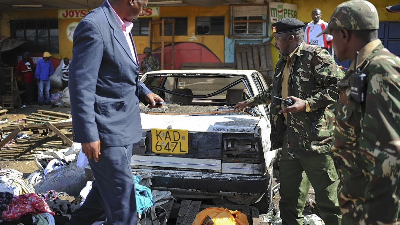 Security forces inspect the scene at the site where two blasts detonated, one in a mini-van used for public transportation, in a market area of Nairobi, Kenya