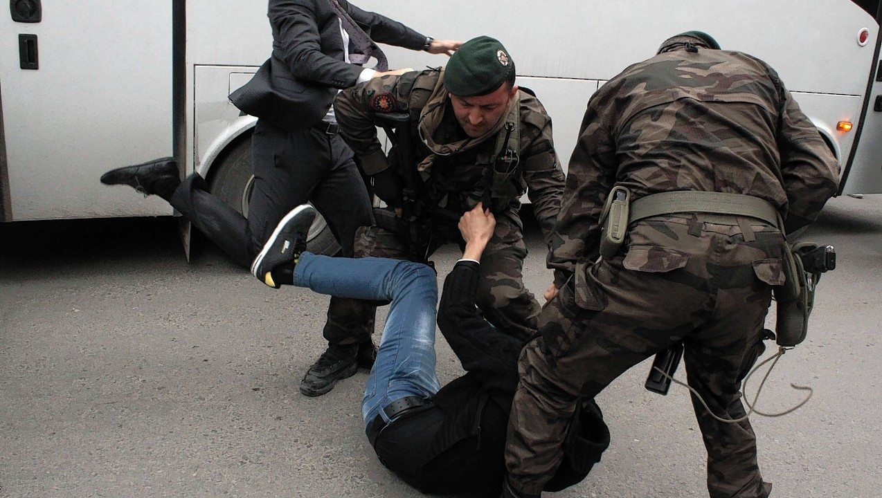 Yusuf Yerkel, advisor to Turkish Prime Minister Recep Tayyip Erdogan, kicks a protester already held by special forces police members during Erdogan's visiting  Soma, Turkey.