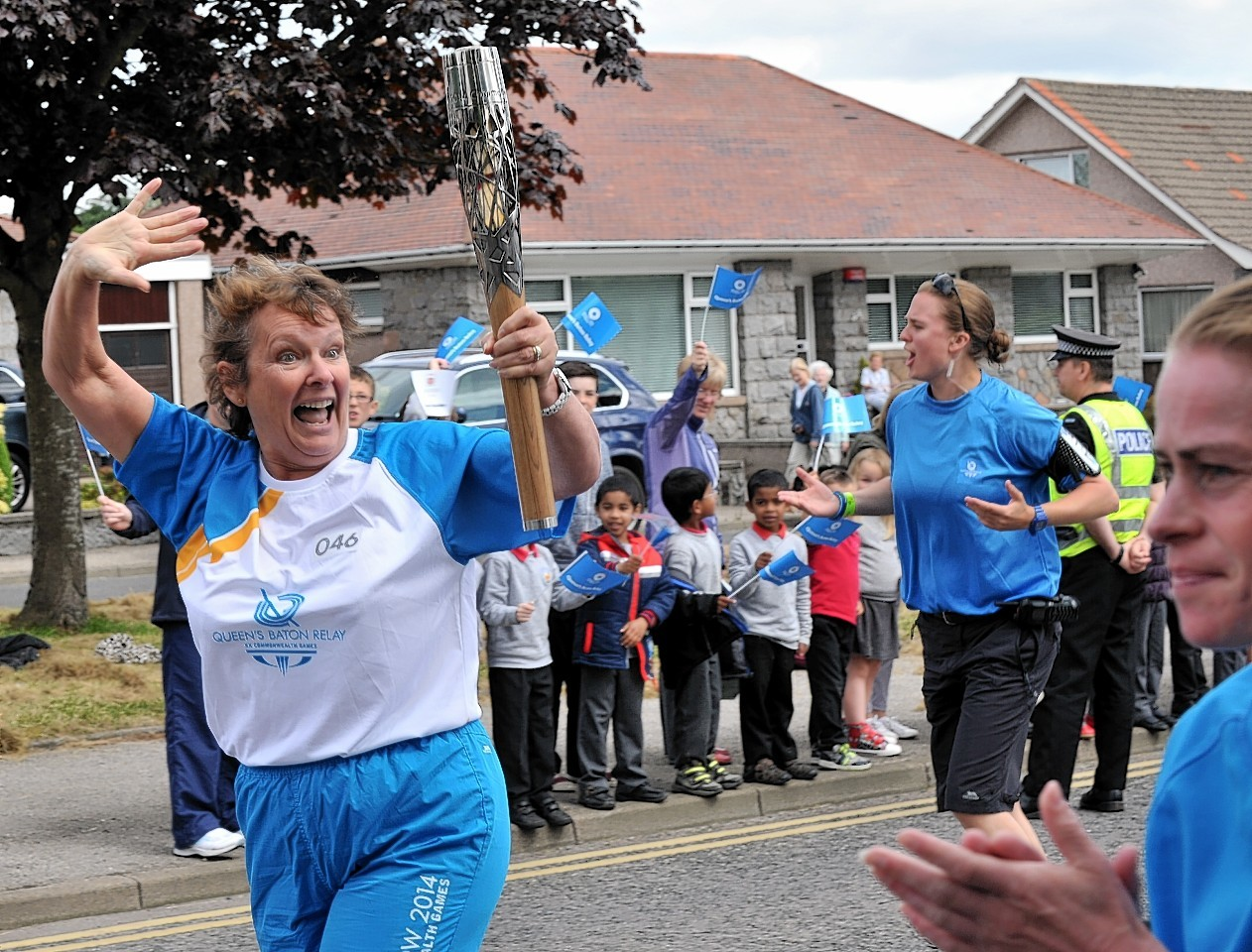 A batonbearer is cheered on by pupils from Fernielea Primary as she makes her way along the Kings Gate, Aberdeen.