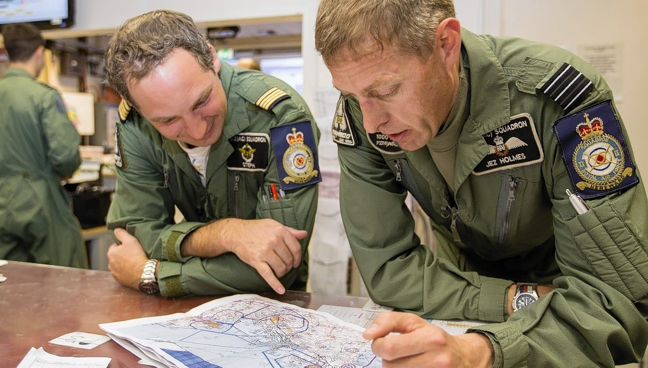 French Air Force pilot Commadant Stephane Peubez (right) and Officer Commanding II (Army-Co-Operation) Squadron, Wing Commander Jez Holmes (left) debriefing their flight over the D-Day beaches, as the two British jets recreated reconnaissance photos of the D-Day beaches in France in a bid to highlight the meticulous planning behind the landings.