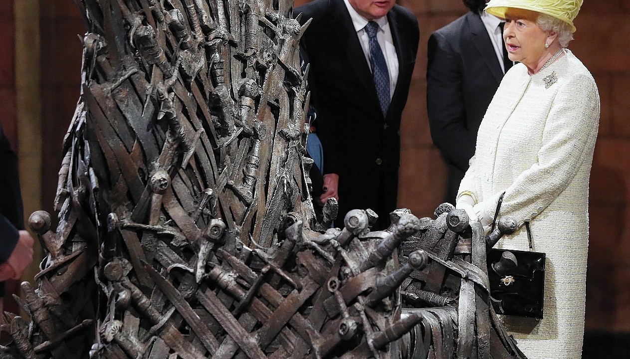 Queen Elizabeth II meets cast members of the HBO TV series 'Game of Thrones' Lena Headey and Conleth Hill as she views some of the props including the Iron Throne on the set of Game of Thrones in Belfast's Titanic Quarter