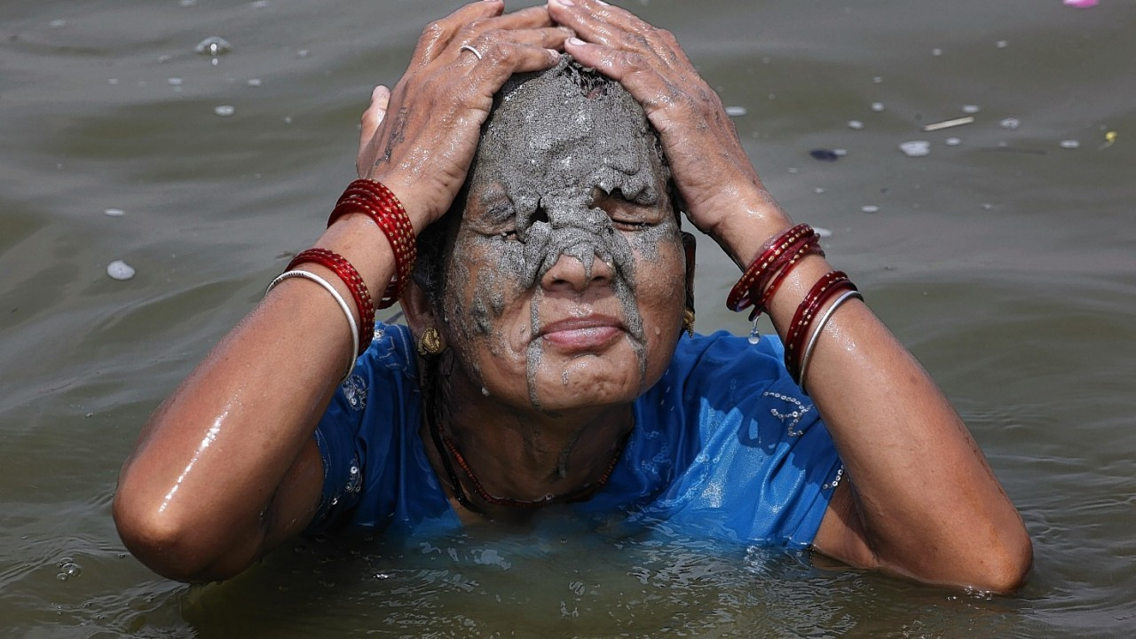 A strong heat has the northern plains of India in its grips with temperatures crossing 45 degree Celsius in several places. A woman puts mud on her face as she bathes in the river Ganges on a hot summer afternoon in Allahabad.