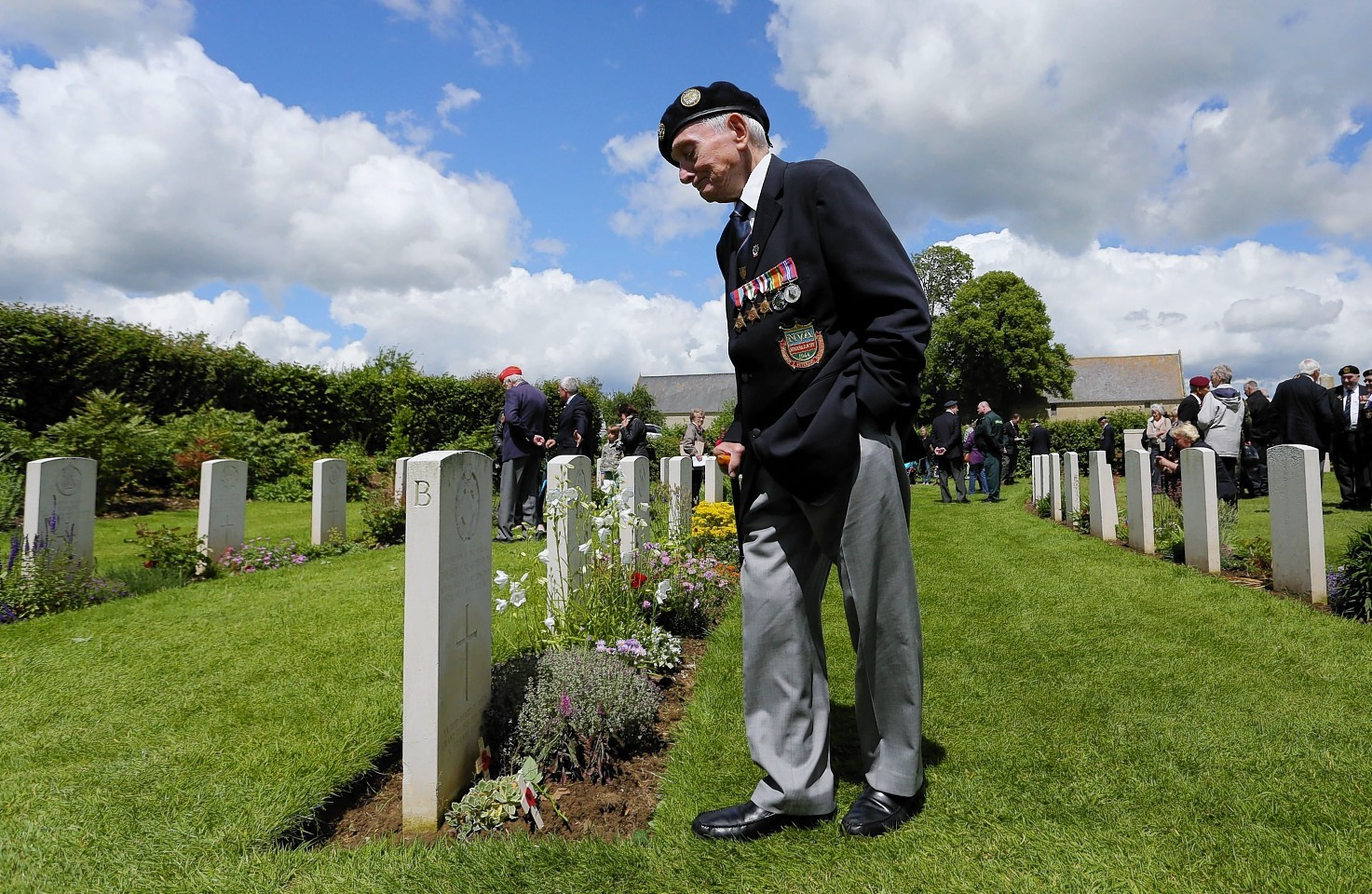 A member of the Normandy Veterans Association takes time to view the headstones at Jerusalem Cemetery in Chouain, France, during a commemorative ceremony to mark 70th anniversary of the D-Day landings during World War II.