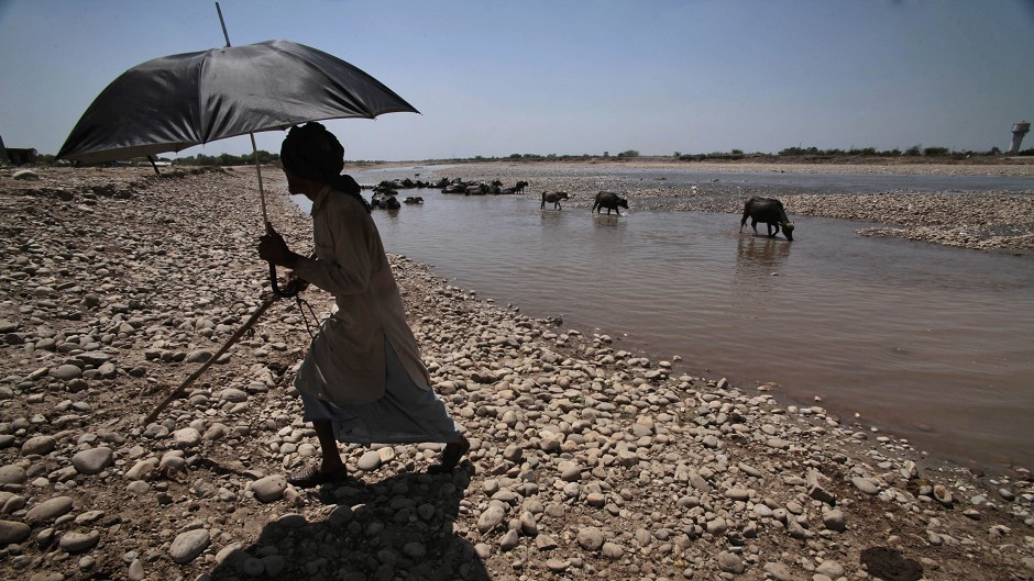 A man holds an umbrella to shield himself from the sun in India, where temperatures hit 47C (AP)