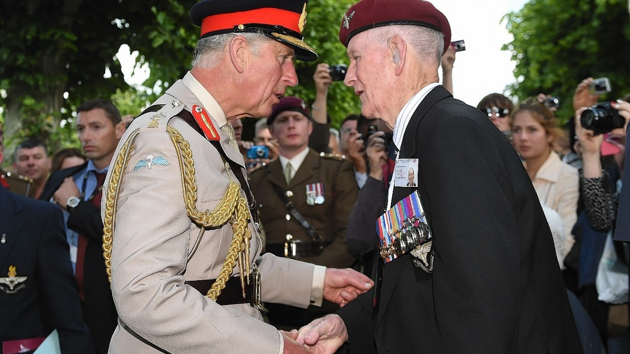 The Prince of Wales meets Normandy veteran James Johnston (right) during a reception at Breville Les Monts in Normandy, France