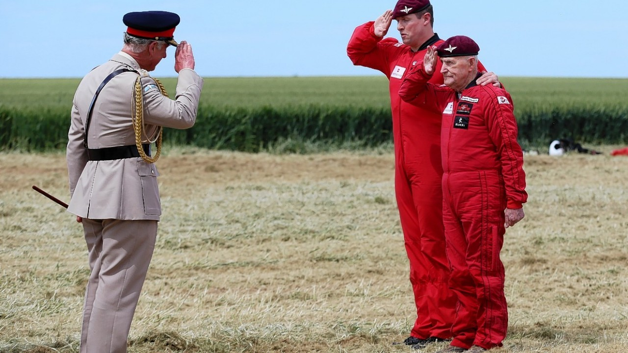 Prince of Wales (right) as he talks to D-Day veteran Jock Hutton and Color Sergeant Billy Blanchard after the veteran took part in a parachute drop onto the same fields near Ranville that were used as a drop zone 70 years ago today to commemorate the involvement of airborne forces in D-Day