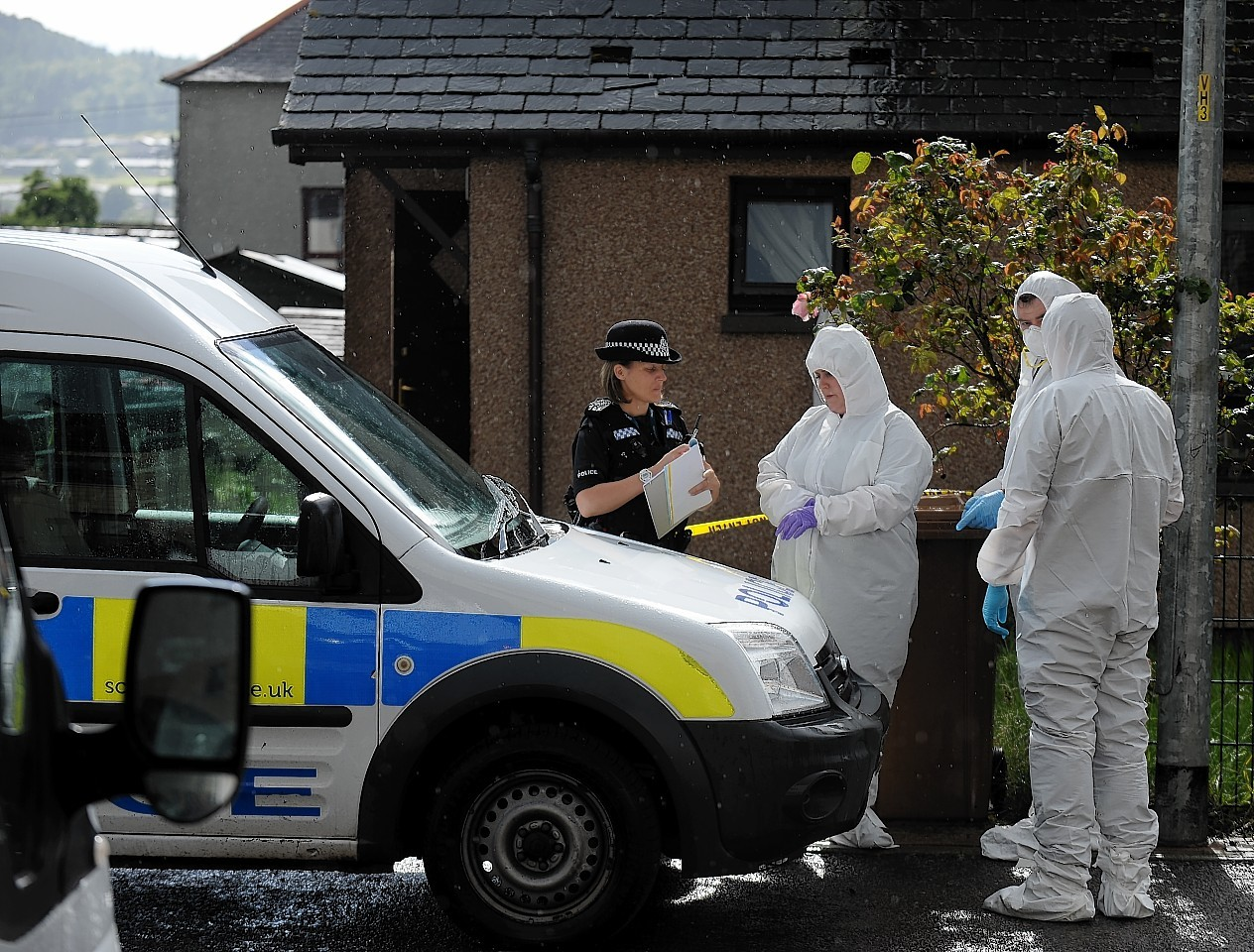 Police in forensic outfits at the home in Inverness