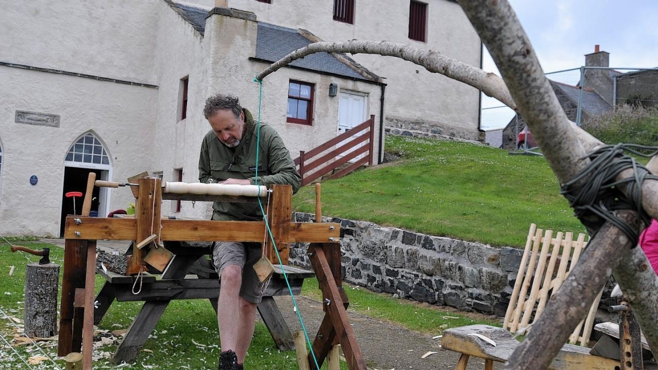 Portsoy Boat Festival.  Ged Connell from Dufftown making wooden whisky tumblers on a traditional pole lathe.