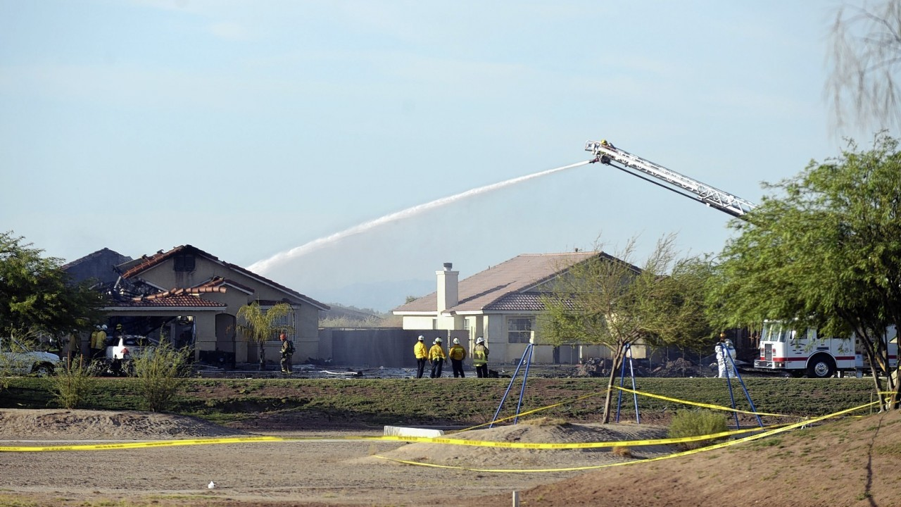 Water is sprayed onto buildings after a Marine jet crashed into a residential area in the desert community of Imperial, Calif., setting two homes on fire Wednesday, June 4, 2014. The pilot ejected safely, and there was no immediate word of any injuries on the ground. The Harrier AV-8B went down at 4:20 p.m. in Imperial, a city of about 15,000 near the U.S.-Mexico border about 90 miles east of San Diego