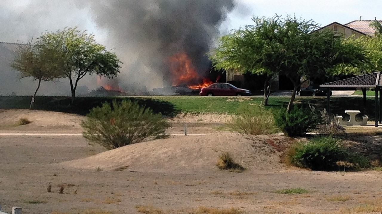 photo provided by Jose Santos shows a fire caused when a military jet crashed in a residential neighborhood in Imperial, Calif