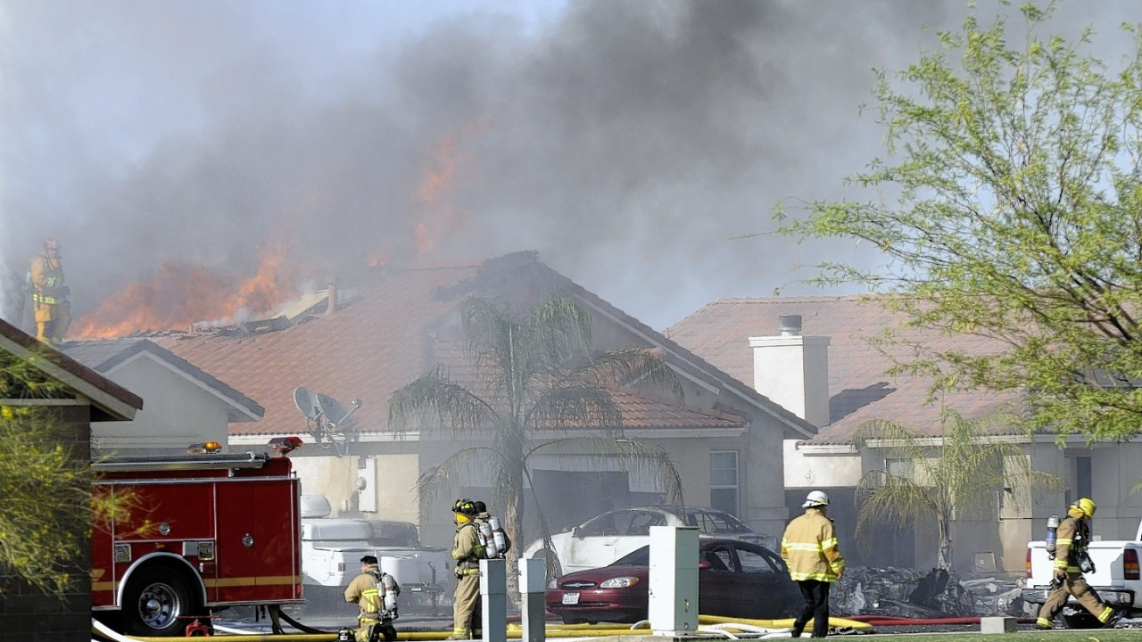 This photo shows the site of a military jet that crashed on a residential street in the desert community of Imperial, Calif