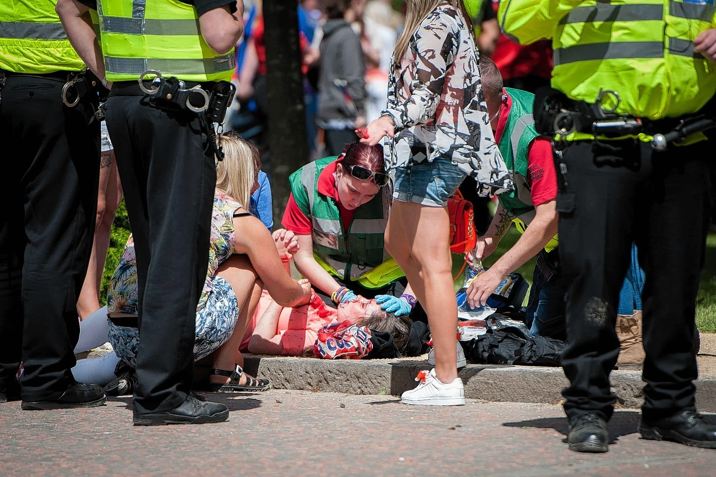 The girl is tended to as she lies on the ground after being hit by a bottle thrown during the parade
