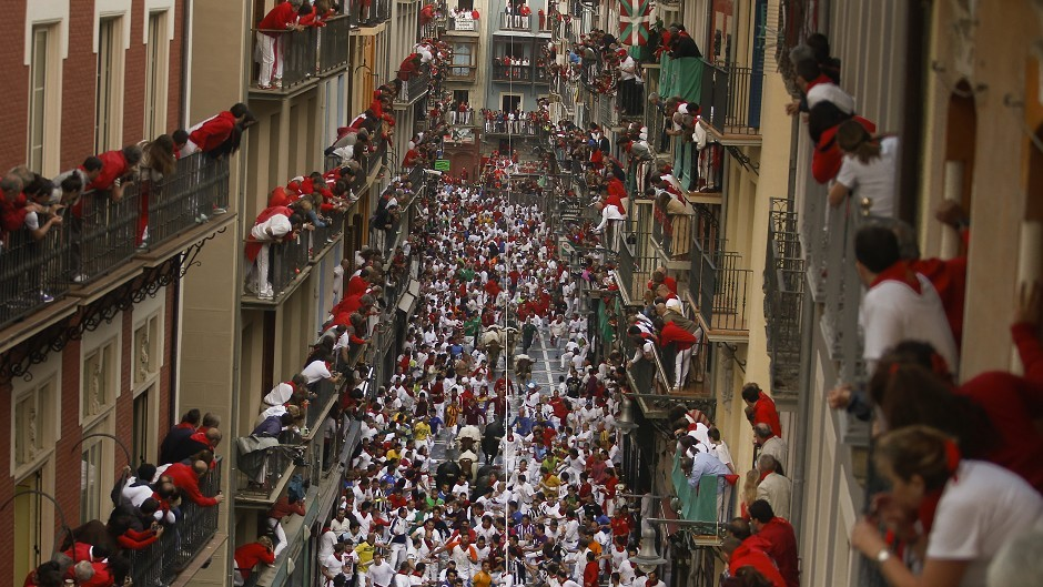 Jandilla fighting bulls run in between revellers as people watch from the balconies during the running of the bulls at the San Fermin festival in Pamplona, Spain (AP)