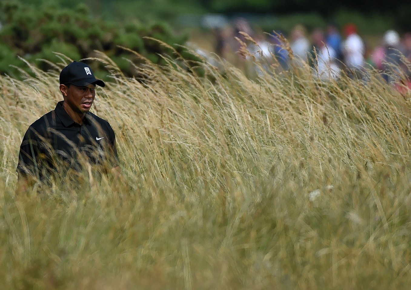 Phil Mickelson plays an iron shot from the rough