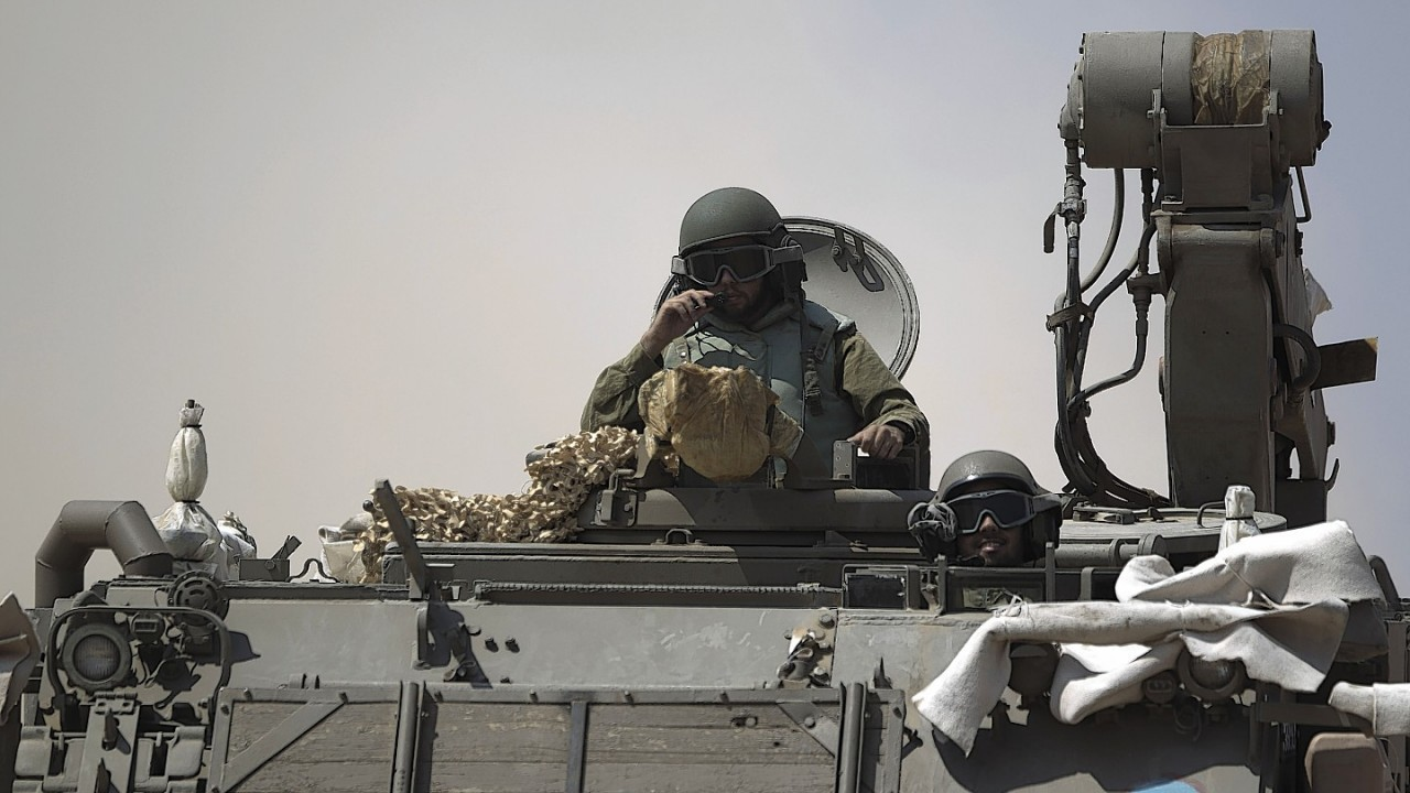 Israeli soldiers drive on an armored personal carrier near the Israel and Gaza Strip border, Monday, July 7, 2014