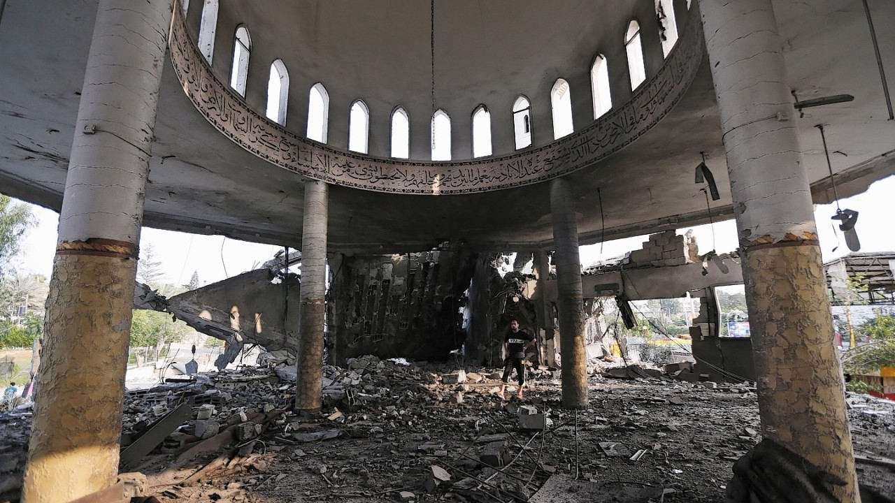Palestinians inspect the damage of the Al-Shalam (Peace) tower, destroyed by an overnight Israeli strike, in Gaza City, Tuesday, July 22, 2014