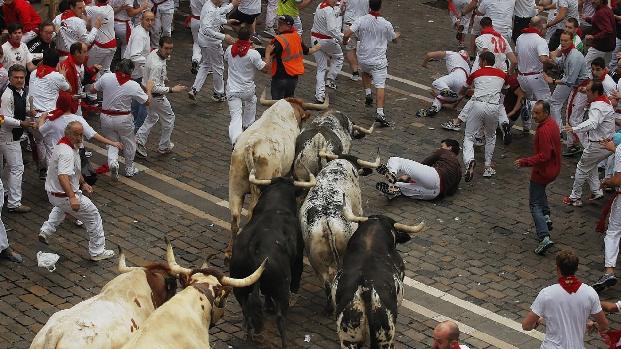 Torrestrella fighting bulls and revelers run during the running of the bulls of the San Fermin festival, in Pamplona, Spain, Monday, July 7, 2014