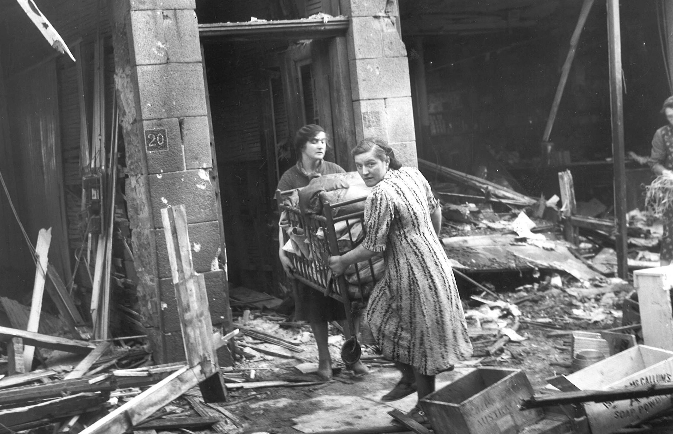 Tenants of a bomb-struck building carry out a crib