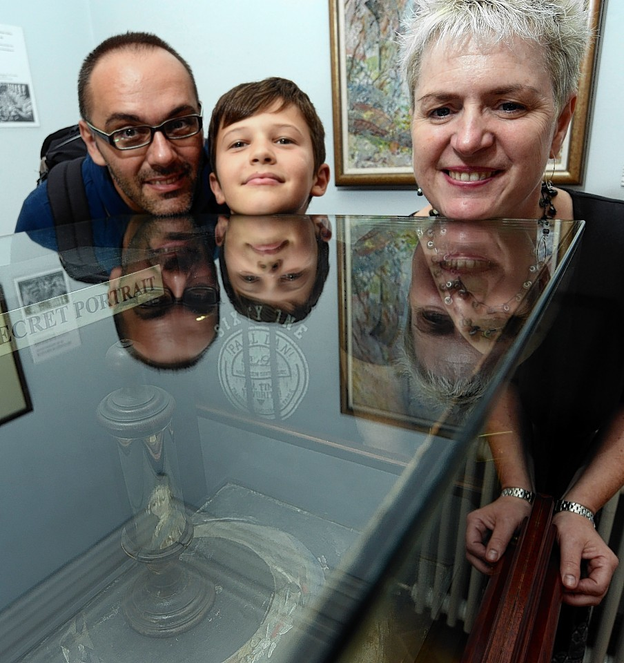 Millionth visitor Marco Novembre views the secret portrait with his son Tommaso and museum manager Colleen Foggo