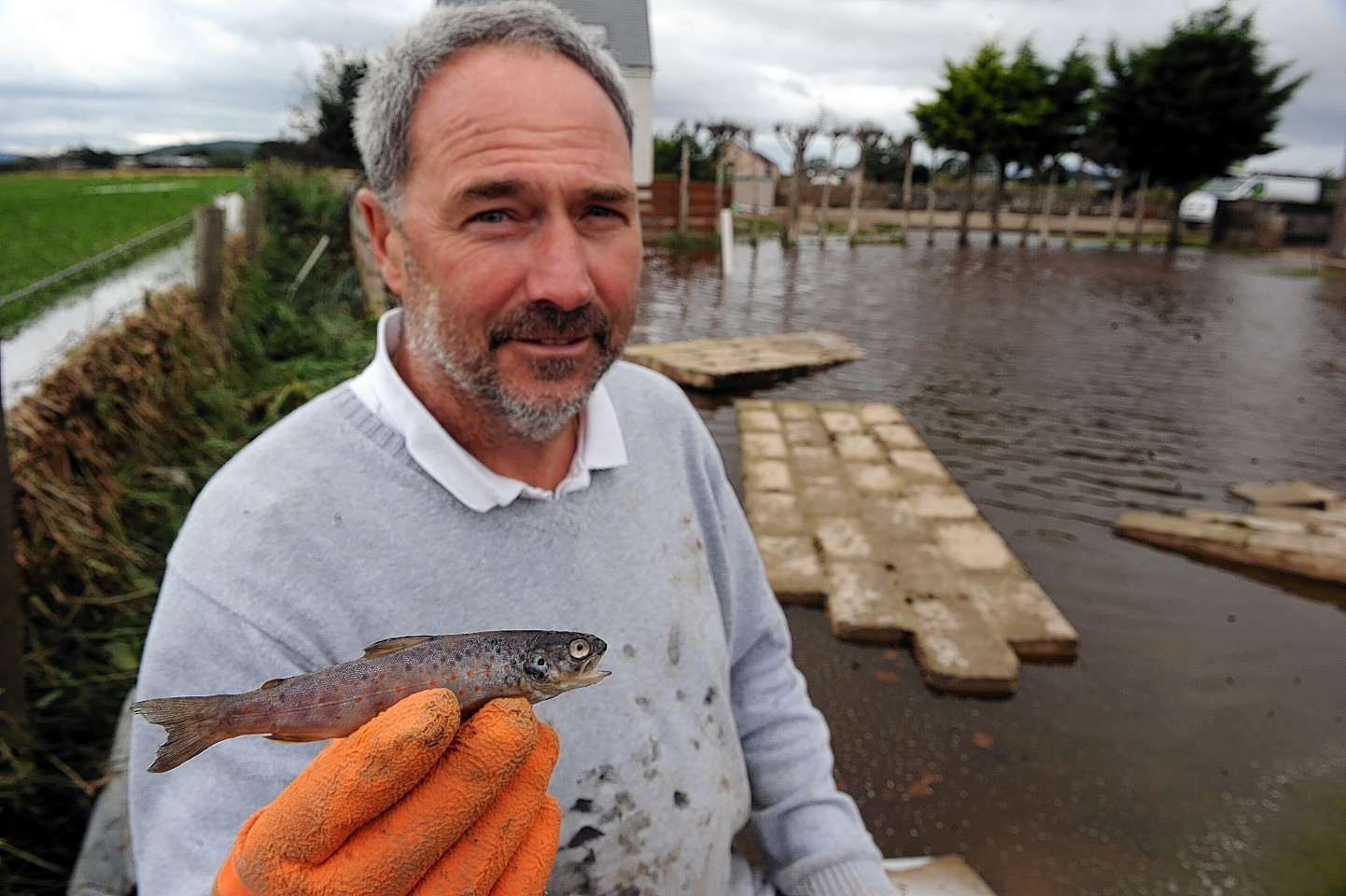 Graeme Lees shows the salmon parr he found in the flood water