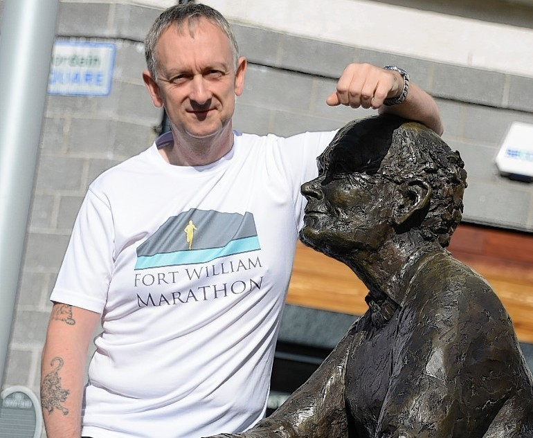 """Chris Millard with the """"sore feet"""" statue in Fort William"""