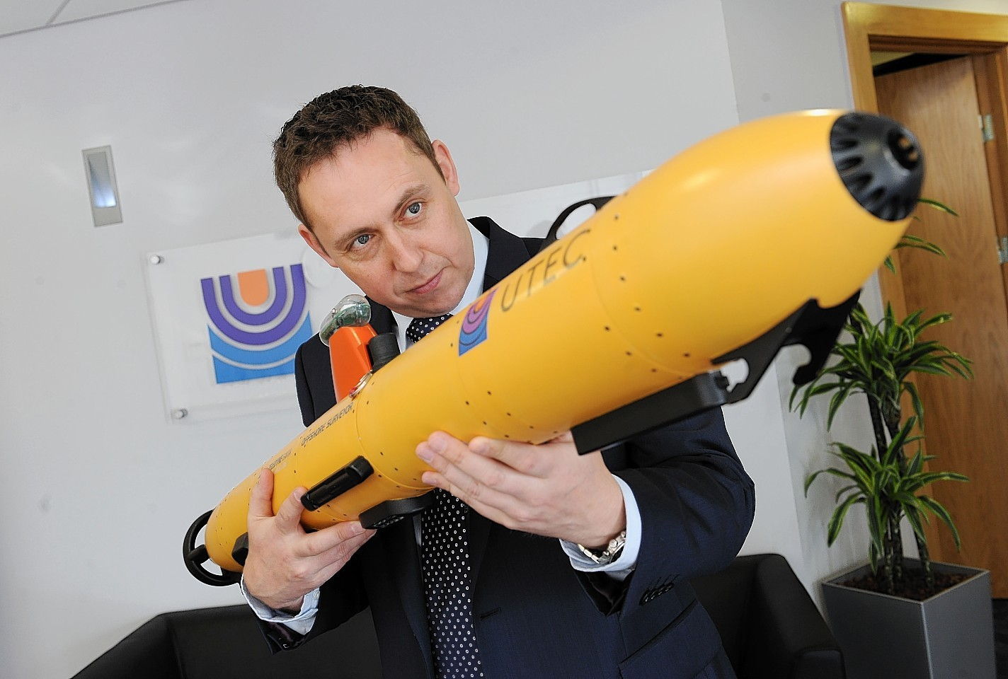 Utec's Kevin McBarron with a scale model of the company's autonomous underwater vehicle technology