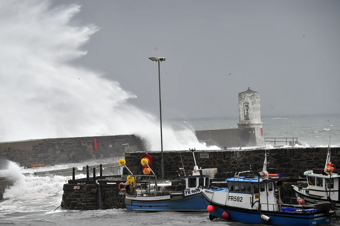 Waves from the Moray Firth batter Rosehearty Harbour yesterday