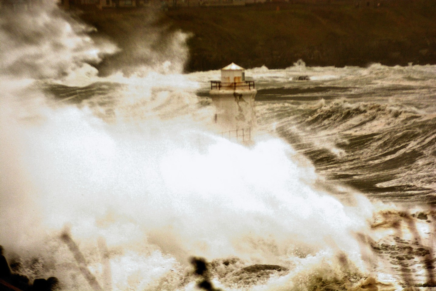 Waves engulf a lighthouse in Wick yesterday