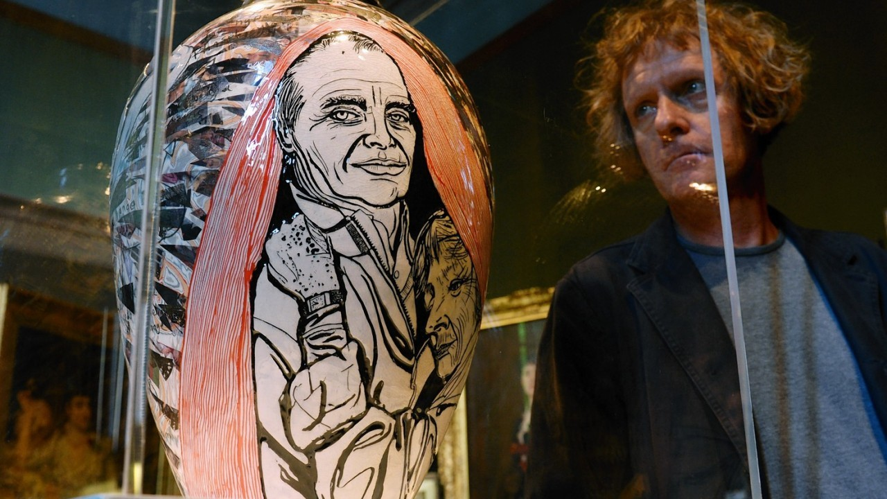 Grayson Perry poses beside 'Memory Jar'  at the National Portrait Gallery